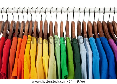 Rainbow colors. Choice of casual clothes on wooden hangers, isolated on white. - stock photo