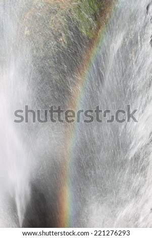Rainbow created by a waterfall - stock photo