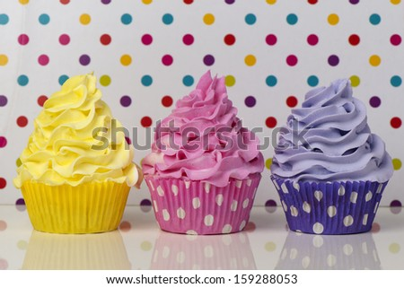 Rainbow cupcakes on a dotted background - stock photo