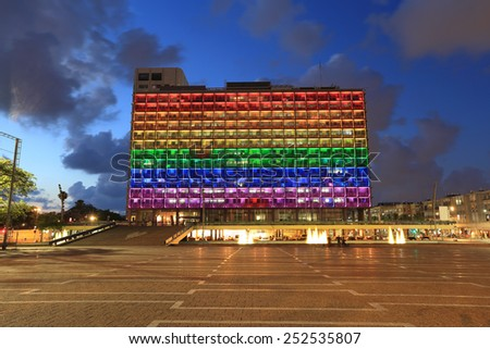 Rainbow flag lighting over Tel Aviv city hall building for pride month - stock photo