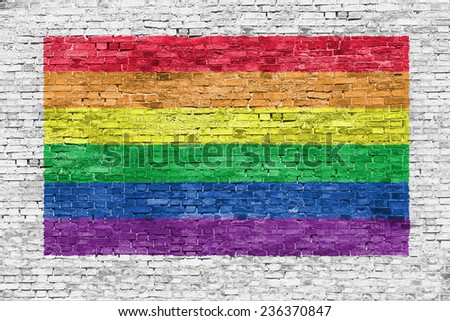 Rainbow flag painted over white  brick wall - stock photo
