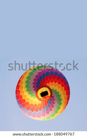 rainbow hot air balloon in a blue sky seen from below - stock photo