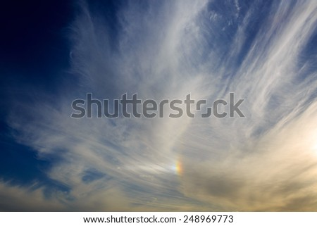 Rainbow in a clouds on blue sky - stock photo