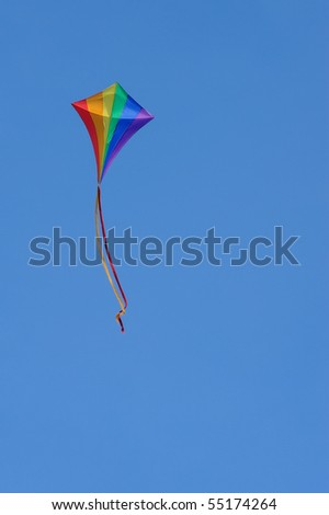 rainbow kite flying in a clear blue sky - similar image with vapor trail in the background also available - stock photo