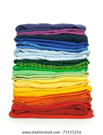 Rainbow laundry. Pile of bright folded clothes on white background. - stock photo