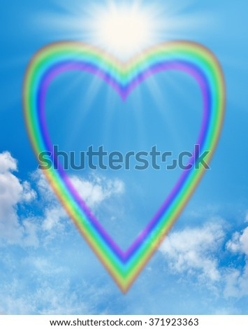 Rainbow love heart blue sky frame - a large empty rainbow shaped heart creating a frame on a blue sky background with a big bright sunburst positioned in the cleavage of the heart - stock photo