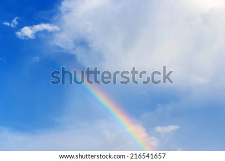Rainbow on a background of blue sky and clouds after  raining - stock photo