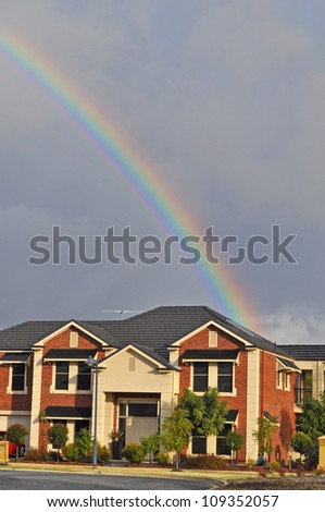 Rainbow on dark sky. Modern Australian house - stock photo