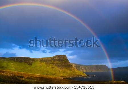 Rainbow over a dramatic coast of Scottish highlands, Isle of Skye, United Kingdom - stock photo