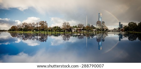 rainbow over melbourne city reflected in the yarra river on a winter day - stock photo