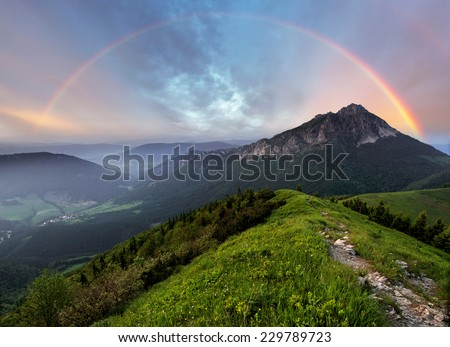 Rainbow over mountain peak - stock photo