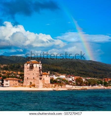 Rainbow over Ouranoupolis (Ouranoupoli), entry site to monasteries of Mount Athos, Greece - stock photo