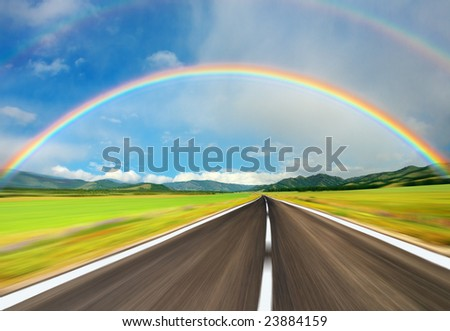 Rainbow over road - stock photo