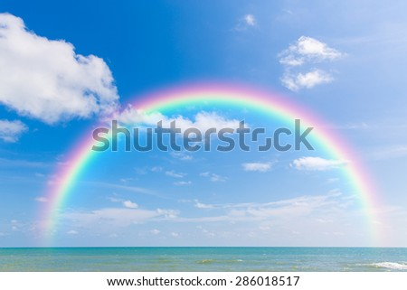 Rainbow over sea with blue sky and cloud. - stock photo