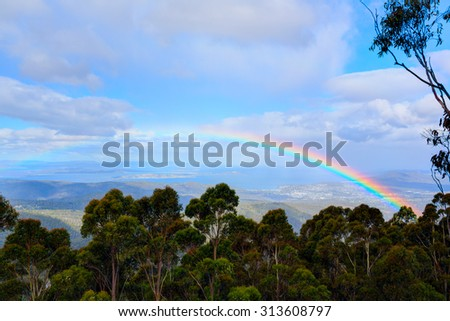 Rainbow over the rainforest. Vicinity of Hobart town, Australia. - stock photo