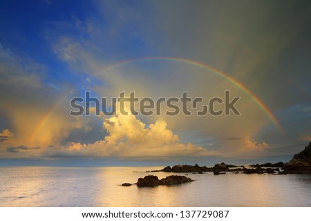 Rainbow over the sea and rock - stock photo