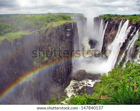 Rainbow over Victoria Falls on Zambezi River, border of Zambia and Zimbabwe - stock photo