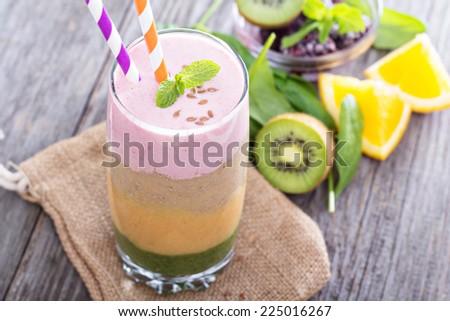 Rainbow smoothie with strawberry, banana, peach, orange, spinach and kiwi - stock photo