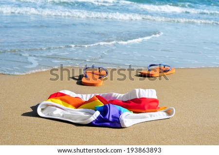 rainbow swimsuit and orange flip-flops in the sand of a beach - stock photo