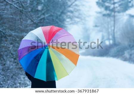 rainbow umbrella in cold winter nature - stock photo
