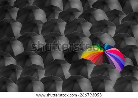 rainbow umbrella in mass of black umbrellas, different concept - stock photo