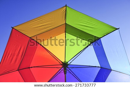 Rainbow Umbrella in the sun - stock photo