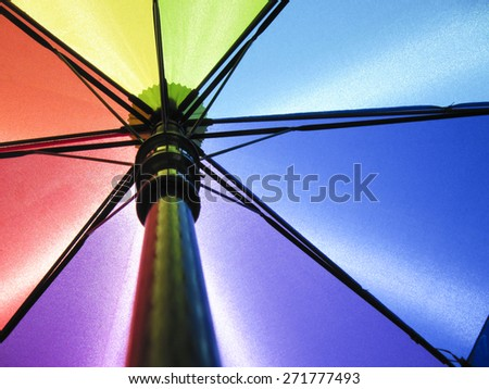 Rainbow Umbrella with Sun Shining through - stock photo