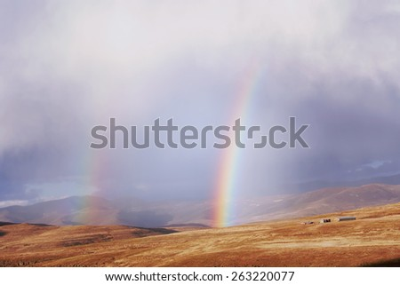 Rainbows above the wheat field in mountains - retro. Shot in Lesotho, South Africa.