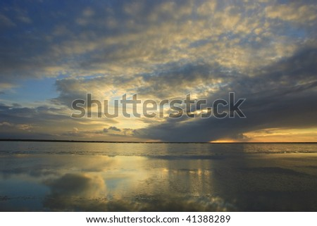 Rainclouds over the horizon at sea during sunset - stock photo