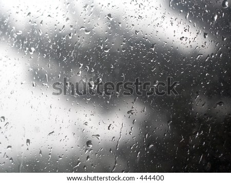 Raindrops against window with blurry tree backdrop - stock photo
