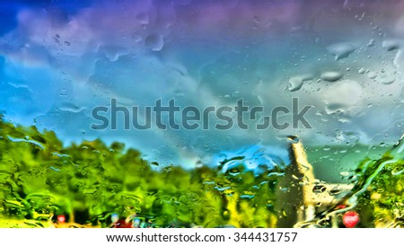 Raindrops create abstract view with rainbow in distance - stock photo