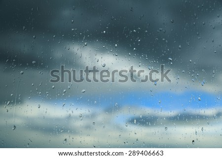 Raindrops on a window during bad weather. - stock photo