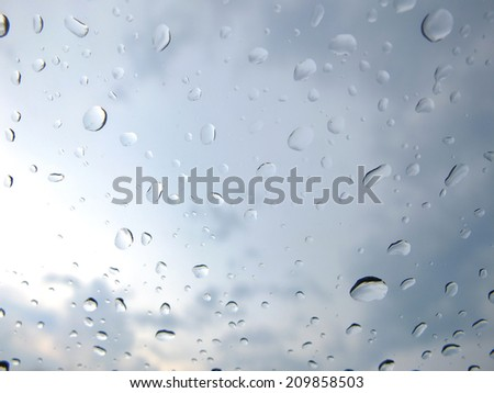 Raindrops on a window pane on a cloudy day. - stock photo