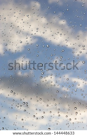Raindrops on a window, with blue sky and clouds behind, as the storm passes. - stock photo