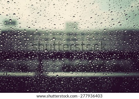 raindrops on the glass with blur building background, vintage tone - stock photo
