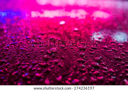 Raindrops on the metal surface in the light colored lights - stock photo