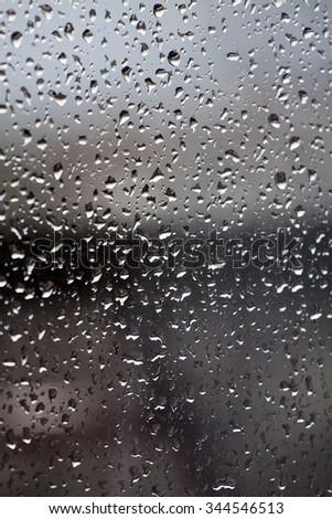 Raindrops on the surface of the dusty window - stock photo