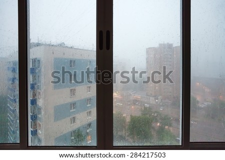 raindrops on urban house window during rain in spring evening - stock photo