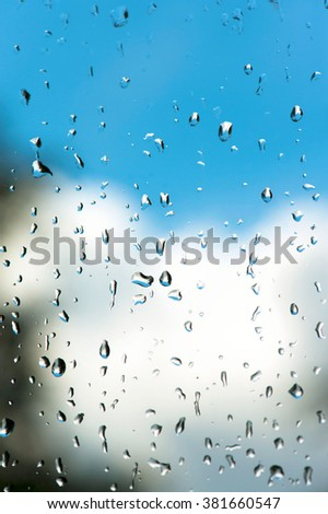 Raindrops on window glass with bright blue cloudy sky background. Vibrant multicolored vertical image. - stock photo