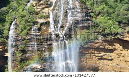 Rainforest - Large waterfall with rainbow in the sunshine - stock photo