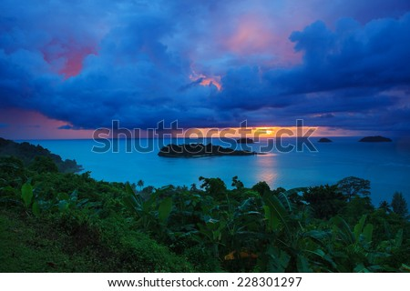 raining clouds and sun set sky behind koh chang island in trat province eastern sea of thailand - stock photo