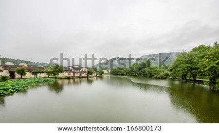Raining days in Hongcun. It's an ancient village near Huangshan, World Heritage Site by UNESCO, has many wonderful traditional Chinese architectures and carvings, red lanterns along the central lake. - stock photo