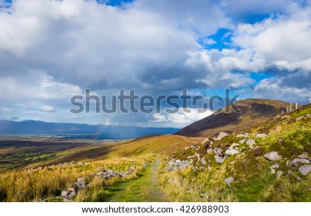 Raining down and sunshine with rainbow on the countryside in Kerry in Ireland - stock photo