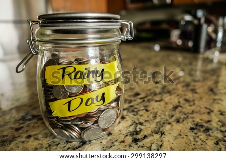 "Rainy Day Money Jar. A clear glass jar filed with coins and bills, saving money. The words ""Rainy Day"" written on the outside. - stock photo"