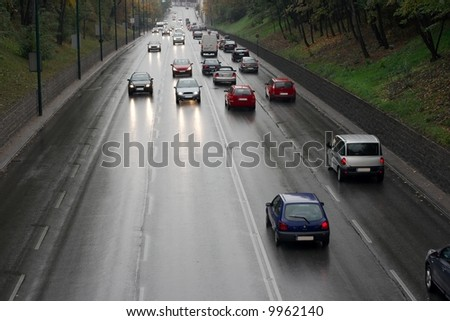 Rainy main road with cars passing by - stock photo