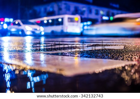 Rainy night in the big city. View of the crossroads at the level of the pedestrian crossing, in blue tones - stock photo