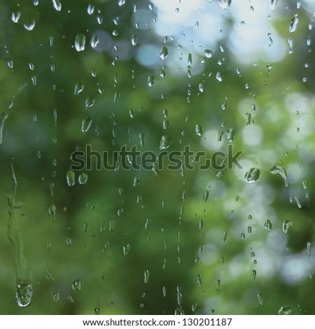 Rainy summer day, raindrops on window glass, macro closeup - stock photo