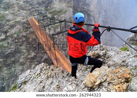 "Rainy weather and climber above suspension bridge along via ferrata ""Brigata Tridentina"", Sella massif, Dolomite Alps, Italy - stock photo"