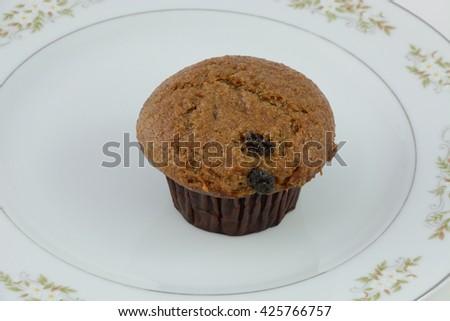 Raisin bran muffin on plate - stock photo