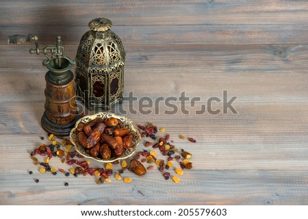Raisins and dates on wooden background. Still life with vintage oriental lantern and mill - stock photo